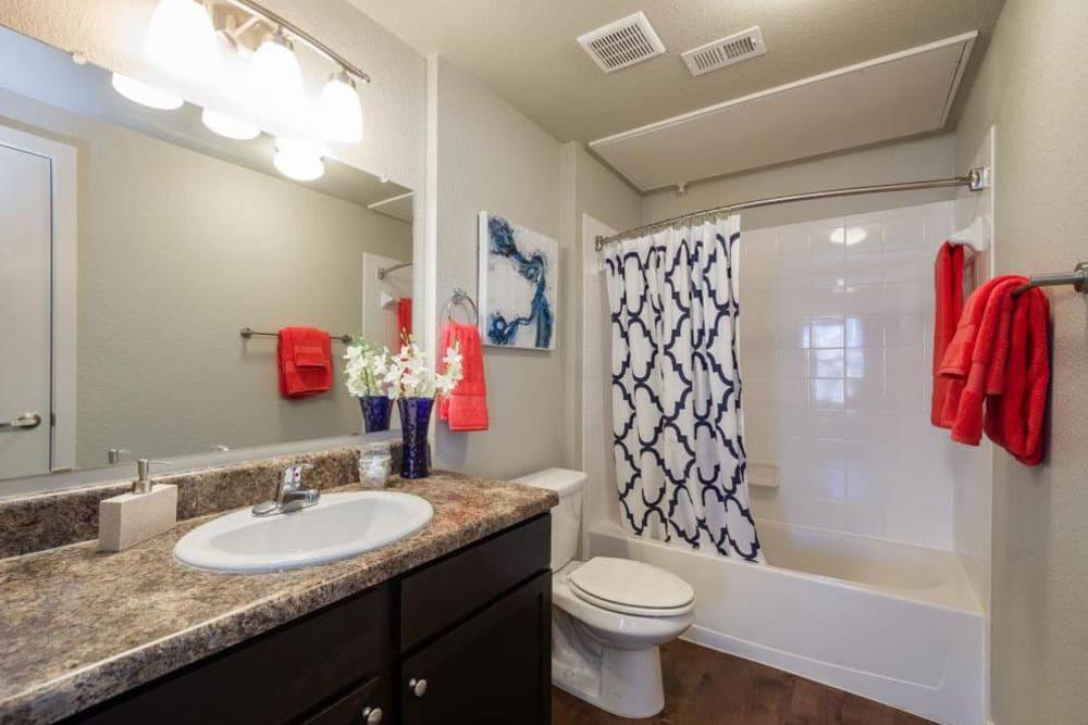 Guest bathroom with large mirror and bath shower combo at Verandas at Alamo Ranch in San Antonio, Texas