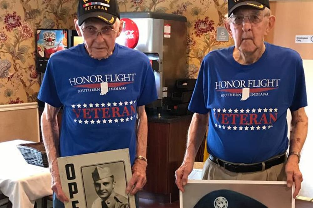 Two veteran residents holding photos of themselves in uniform at BridgePointe Health Campus in Vincennes, Indiana