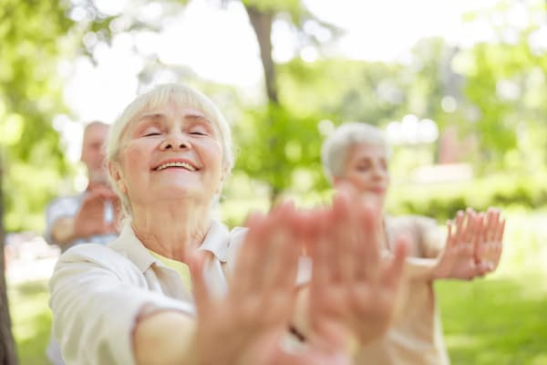 Women doing stretching exercises outdoors at Arbors Memory Care in Sparks, Nevada