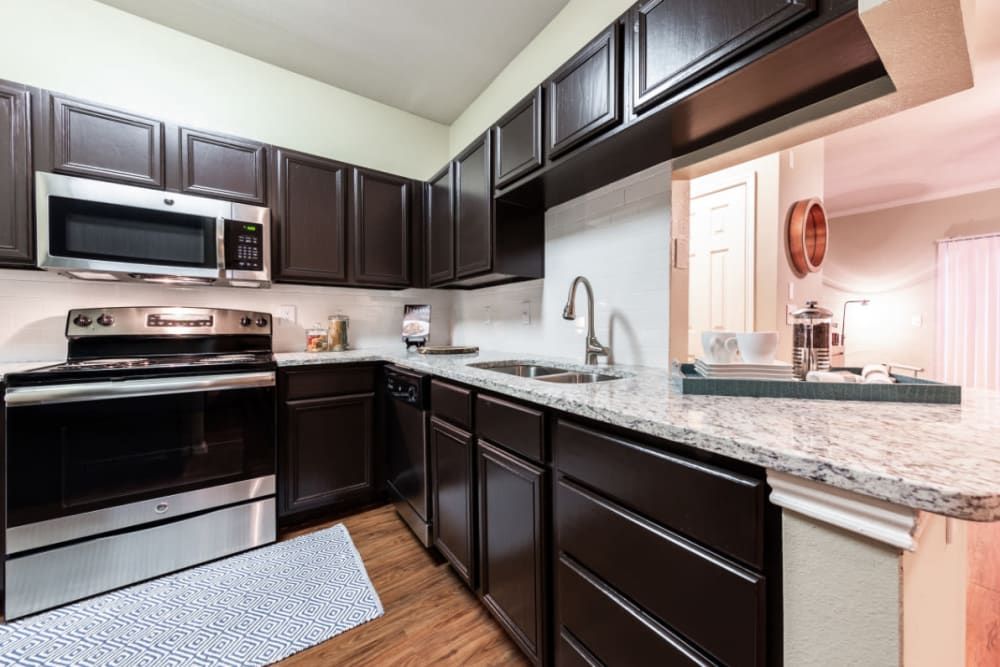 Kitchen with granite counters at Marquis at Ladera Vista in Austin, Texas