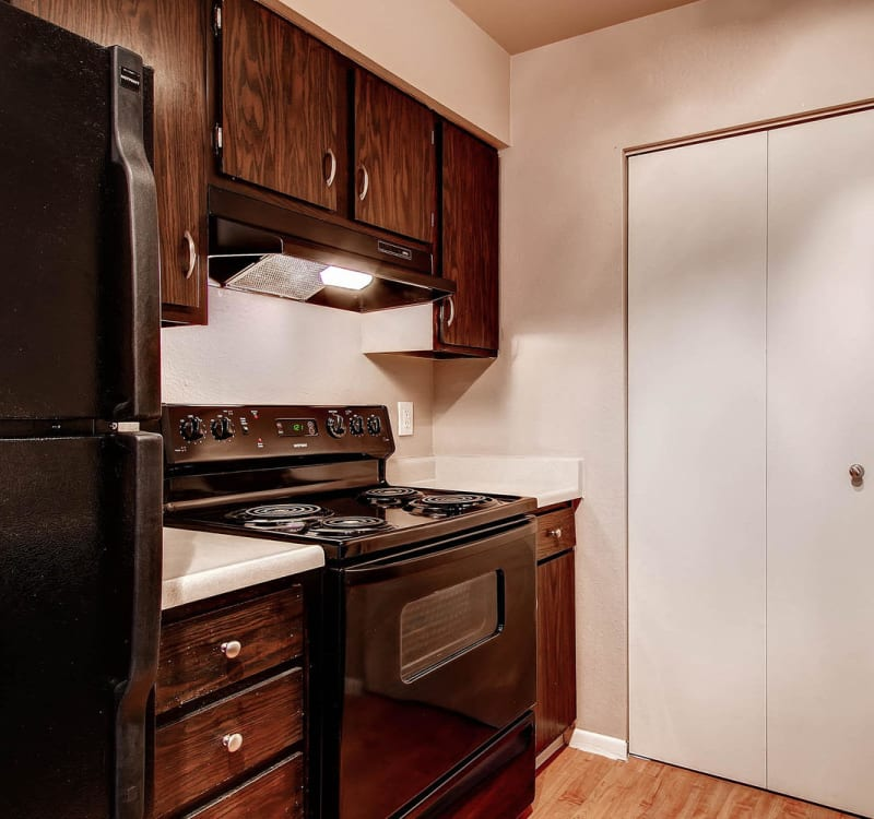 Kitchen with black appliances at Arvada Village Apartment Homes in Arvada, Colorado