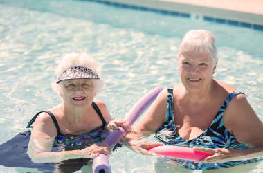 Residents enjoying time in the beautiful pool at Las Palomas Senior Living in Mesa, Arizona