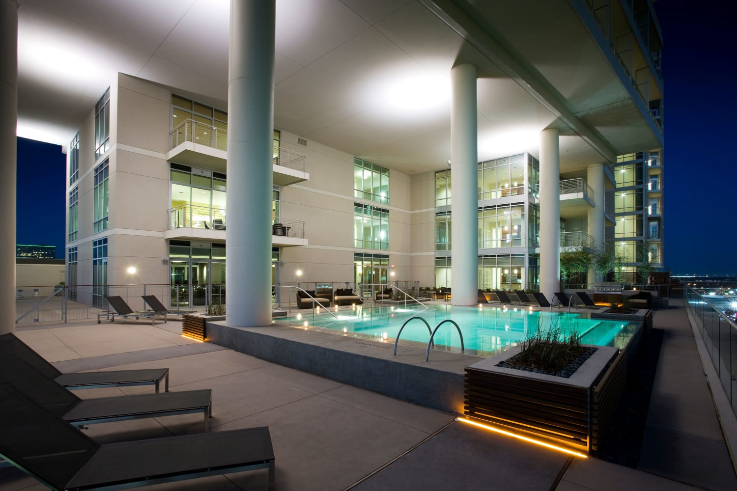 Resort-style swimming pool with lounge chairs at The Heights at Park Lane in Dallas, Texas