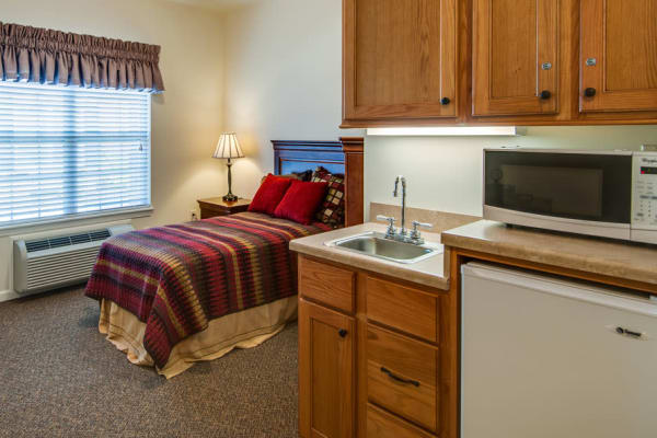 Assisted living apartment bedroom at Maplebrook Senior Living in Farmington, Missouri