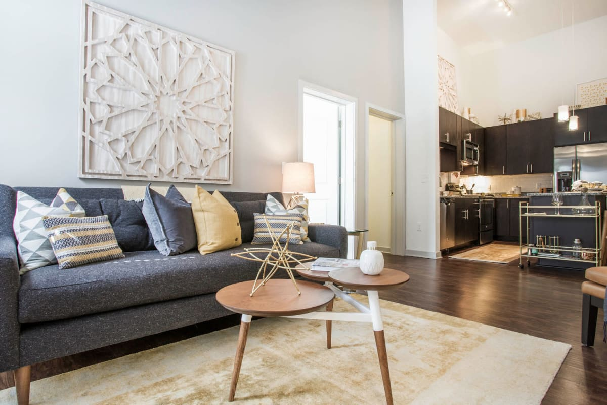 Full size couch with coffee table in living room with rug on wood flooring at Marq Midtown 205 in Charlotte, North Carolina
