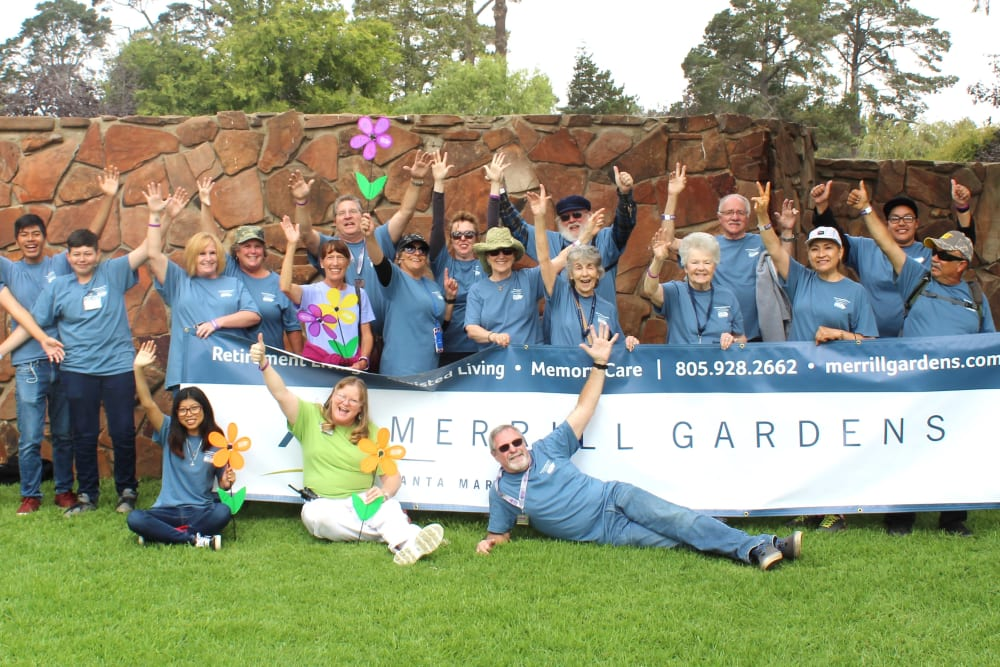 staff and senior residents waving at Merrill Gardens at Santa Maria in Santa Maria, California.