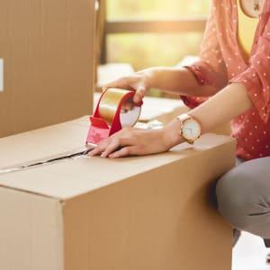 A customer of A-1 Self Storage packs belongings into a box.