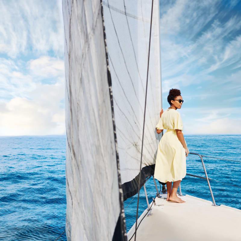 Woman on the bow of a sailboat leaving the marina at Portside Ventura Harbor in Ventura, California