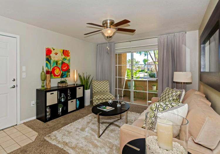 Well-decorated living room with ceiling fan in model home at The Boulevard in Phoenix, Arizona