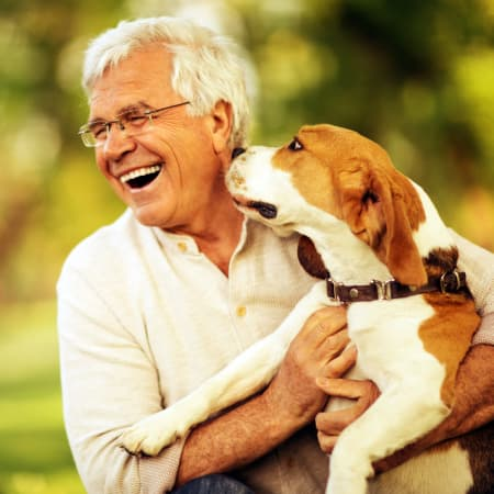 A smiling resident with his dog outside at The Legacy at Hawthorne Park in Greenville, South Carolina