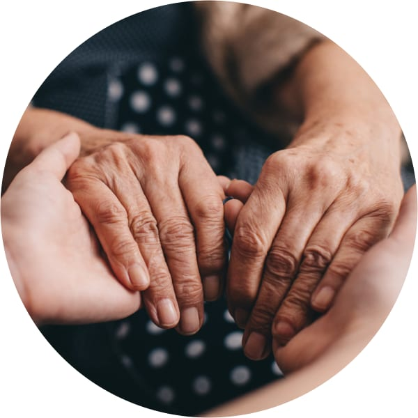 Memory Care resident holding hands with a caretaker at a Oxford Senior Living community