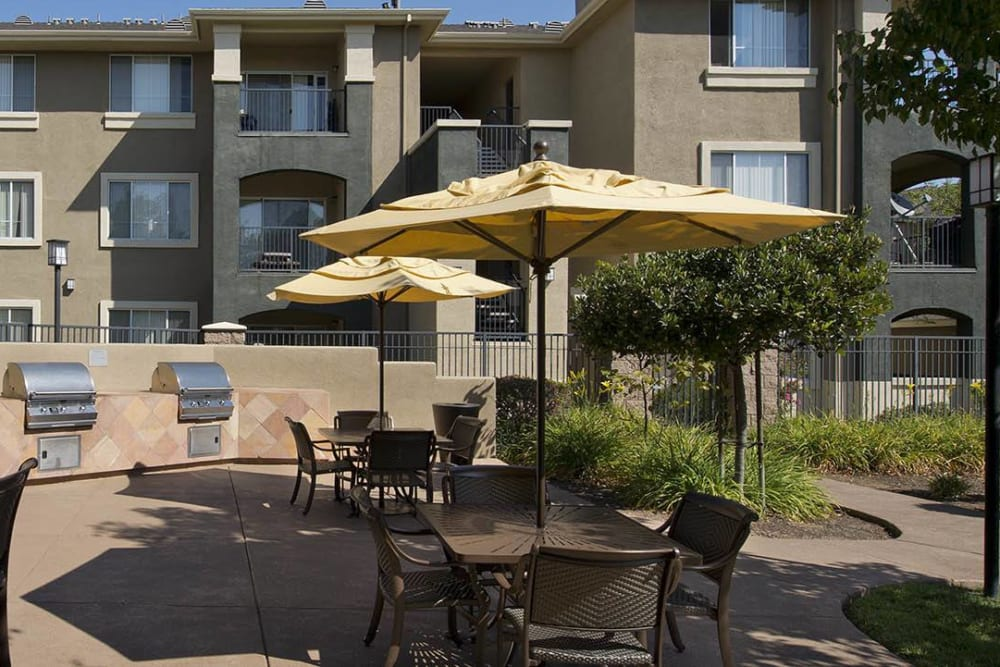 Table and chairs with an umbrella for a poolside lunch at Cross Pointe Apartment Homes in Antioch, California