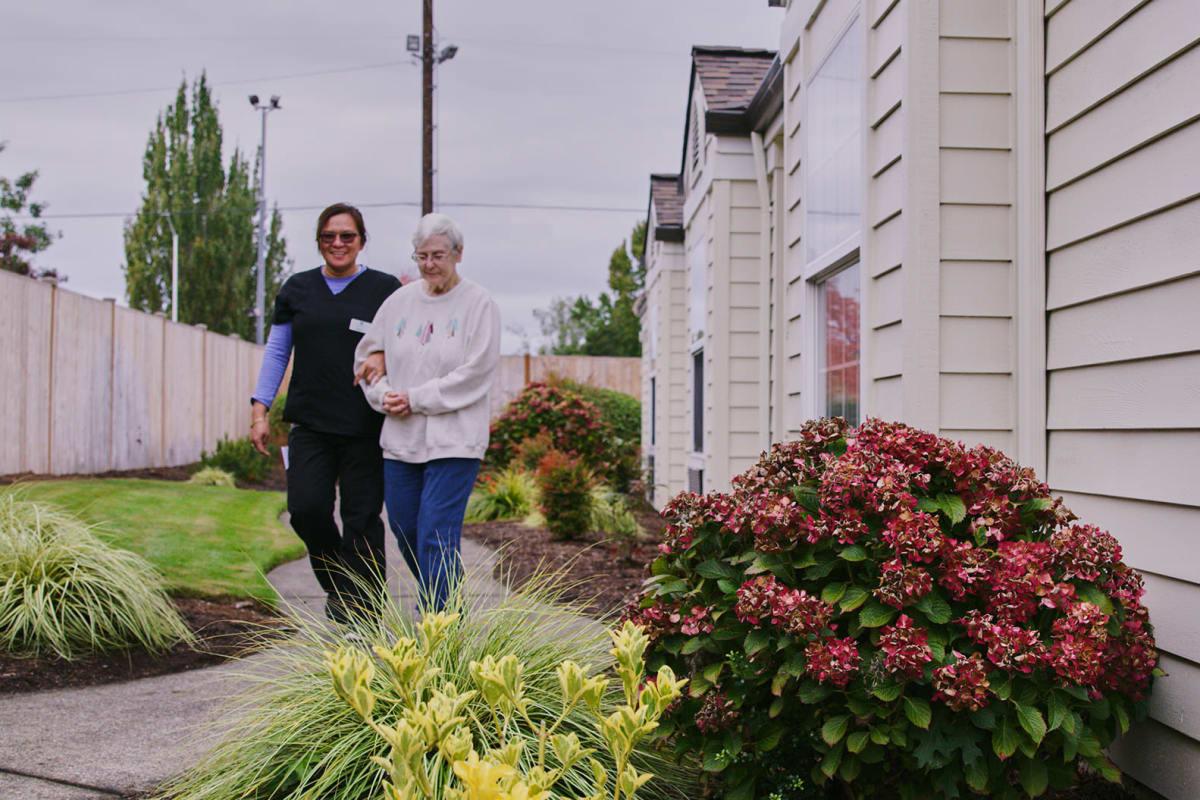 Resident and caretaker outside for a walk at Farmington Square Beaverton in Beaverton, Oregon