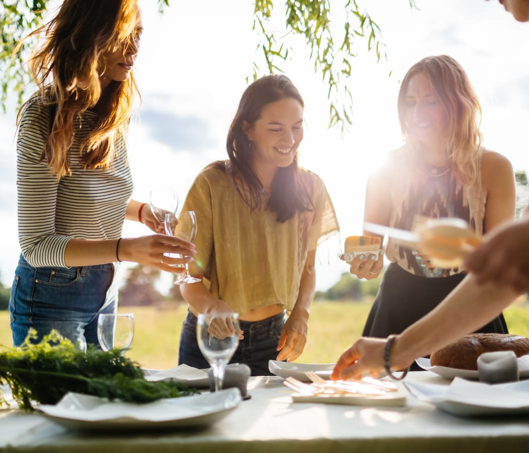 Women preparing a table outside for a dinner party at Veridian Place in Dallas, Texas