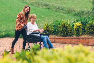Resident being taken on a walk in her wheelchair at Mirror Lake Village Senior Living Community in Federal Way, Washington.