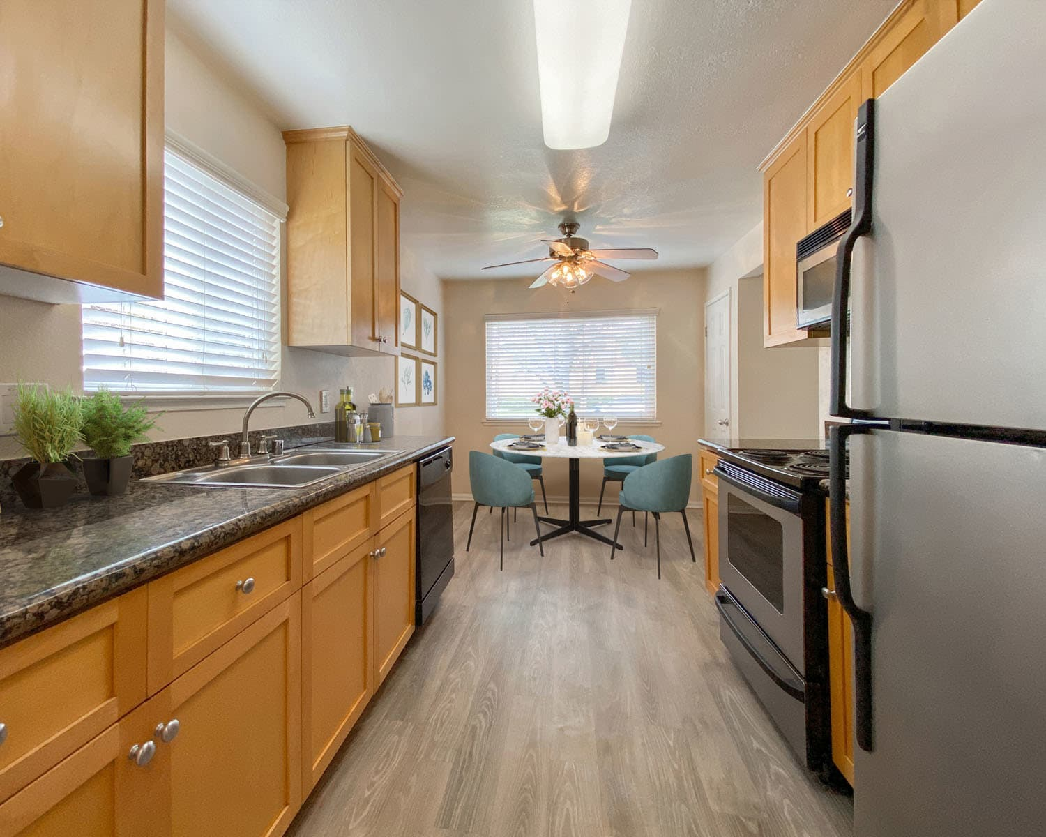 Hardwood flooring and stainless-steel appliances in a model apartment's kitchen at Pleasanton Place Apartment Homes in Pleasanton, California