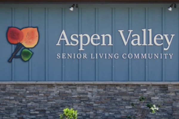 Logo and signage on a wall outside Aspen Valley Senior Living in Boise, Idaho