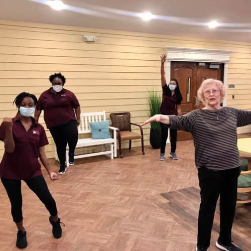 Team member with a resident excercising at Oxford Glen Memory Care at Carrollton in Carrollton, Texas