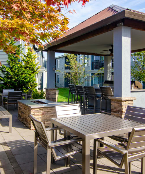 Exterior Common space, covered BBQ, fire-pit, and lounge at The Addison Apartments in Vancouver