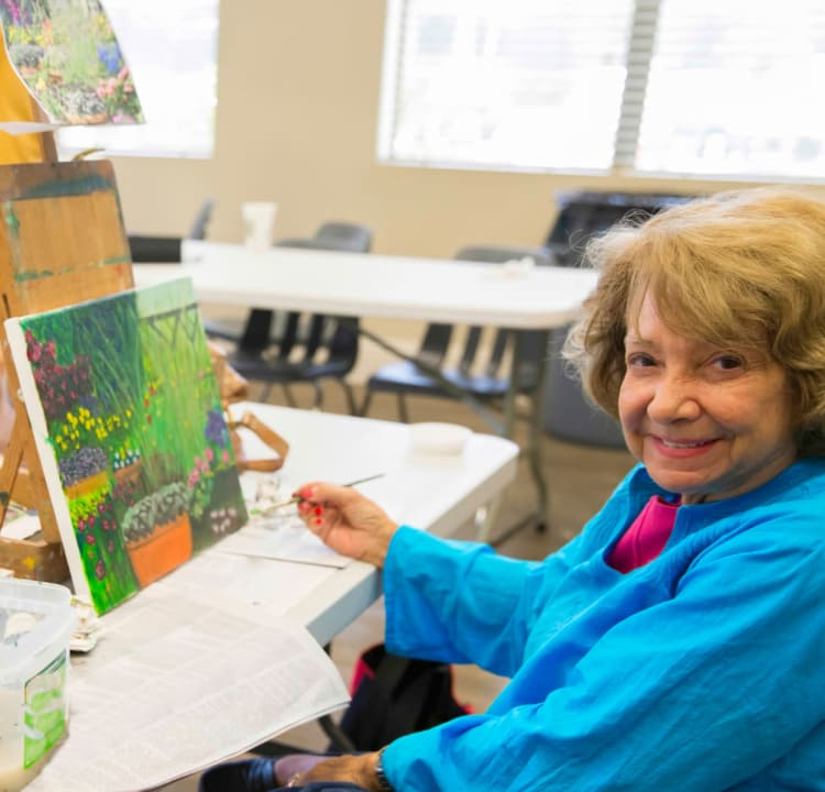 Senior woman painting on canvas at Azpira Place of Breton in Kentwood, Michigan