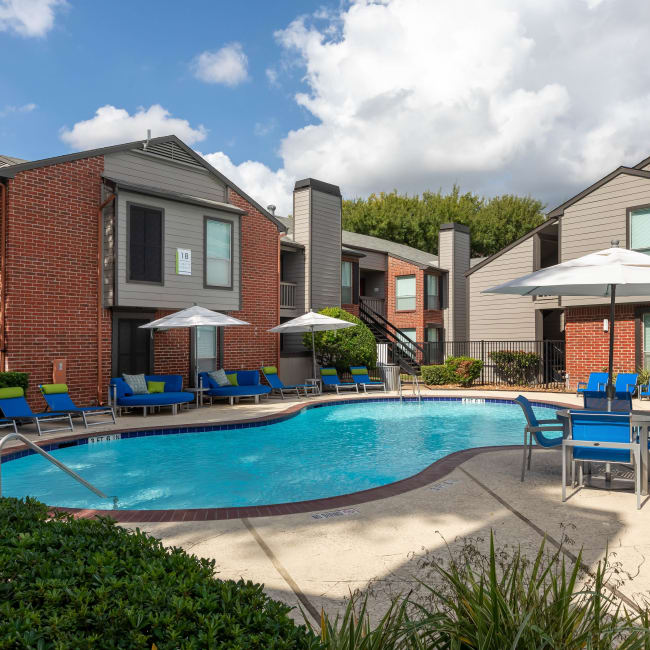 Swimming pool with umbrella covered table and chairs at Finley West in Houston, Texas