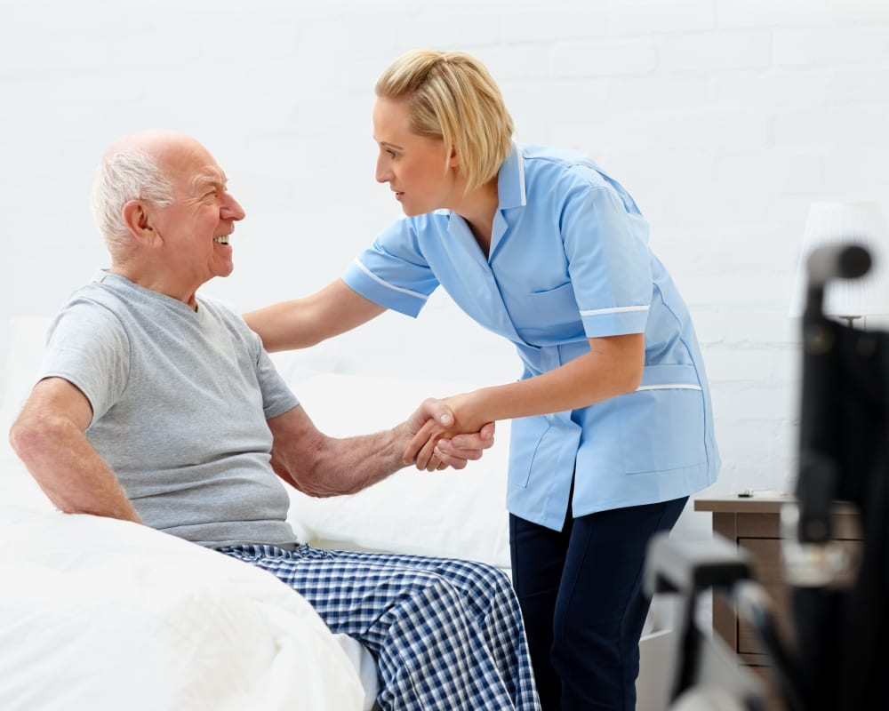 Staff assisting resident out of bed at Milestone Senior Living in Faribault, Minnesota.