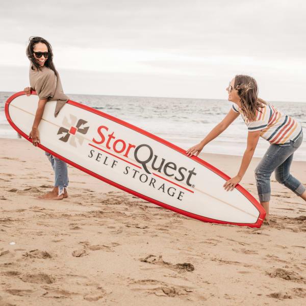 Two women carrying a StorQuest surfboard