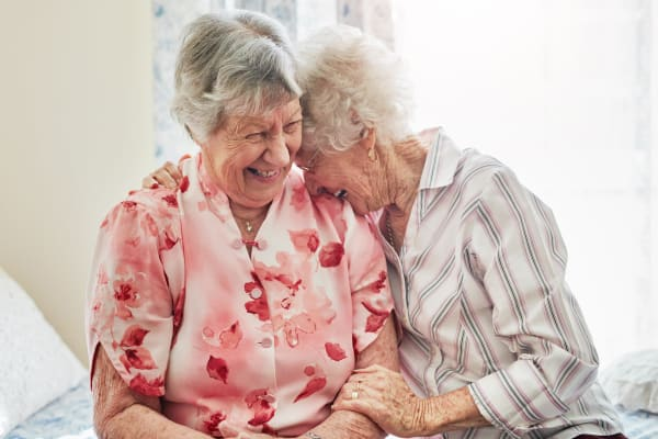 Two senior women laughing together at Peninsula Reflections in Colma, California