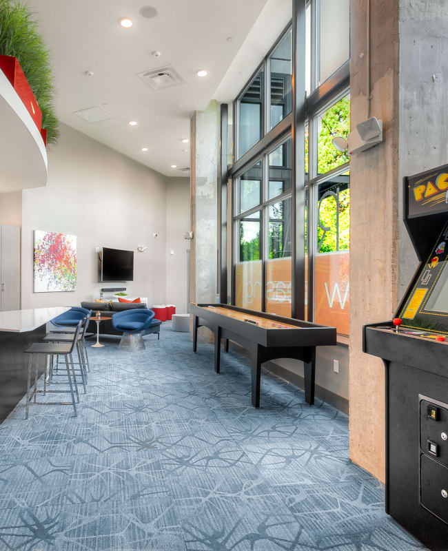 common area clubhouse lounge with couches, tv, shuffleboard, pac-man game, and kitchen at Tria Apartments in Newcastle