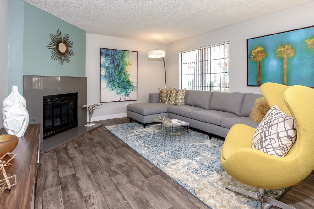 Spacious living room with two large windows and a fireplace at Sonora at Alta Loma in Alta Loma, California