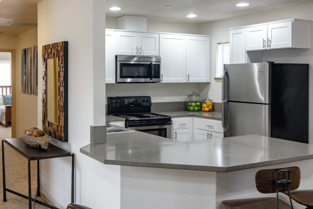 Renovated kitchen with white cabinetry and a hallway view at The Addison Apartments in Vancouver, Washington