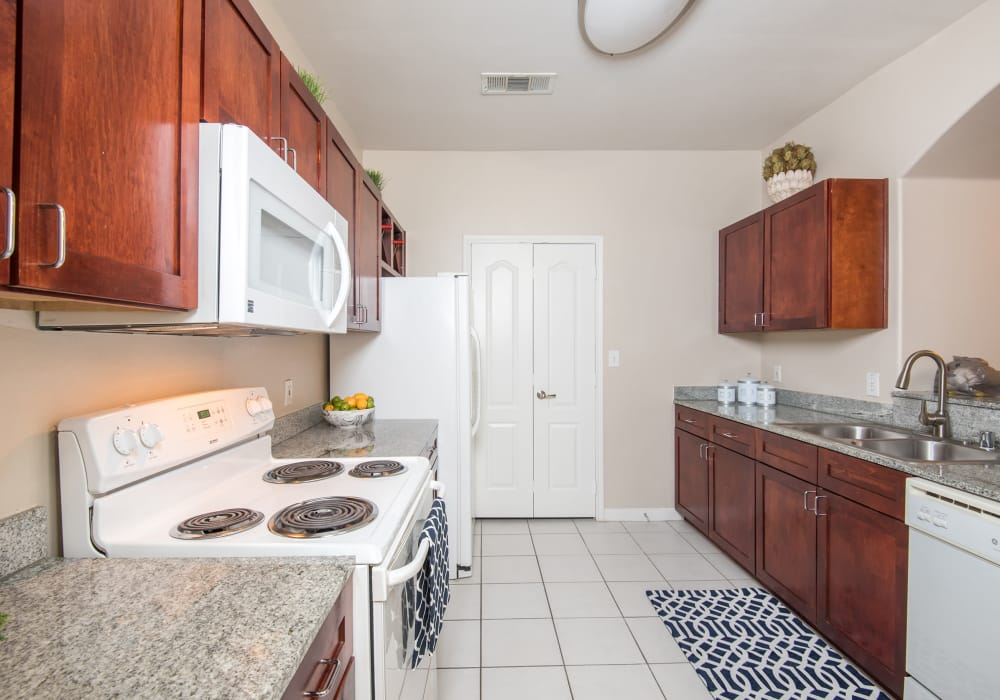 White appliances and granite countertops at Chateau De Ville in Farmers Branch, Texas