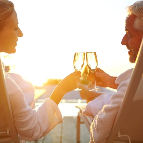 Resident couple outside toasting the good life from their private balcony outside their home at The Coast of Naples Florida in Naples, Florida