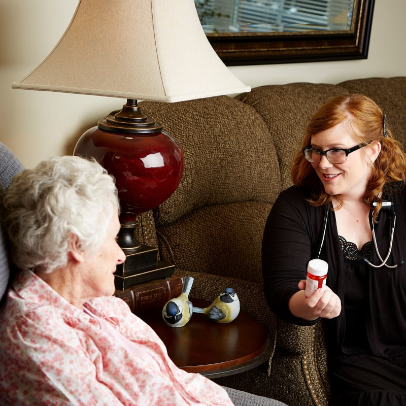 Resident sitting on a couch talking to a nurse at Deer Crest Senior Living in Red Wing, Minnesota