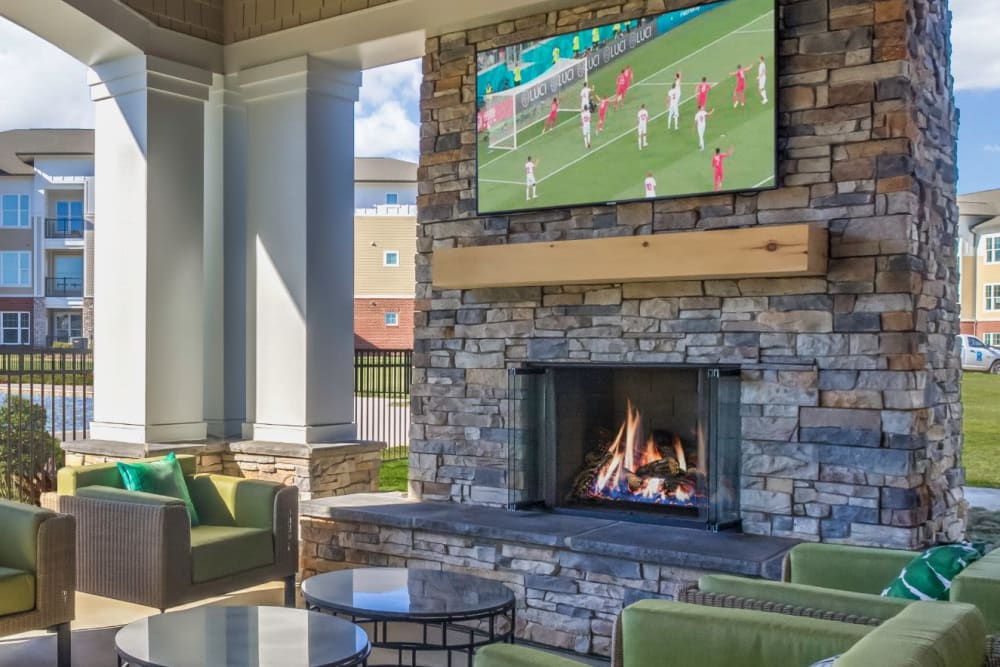Outdoor cabana with a fireplace and flat-screen TV at The Palmer in Charlotte, North Carolina