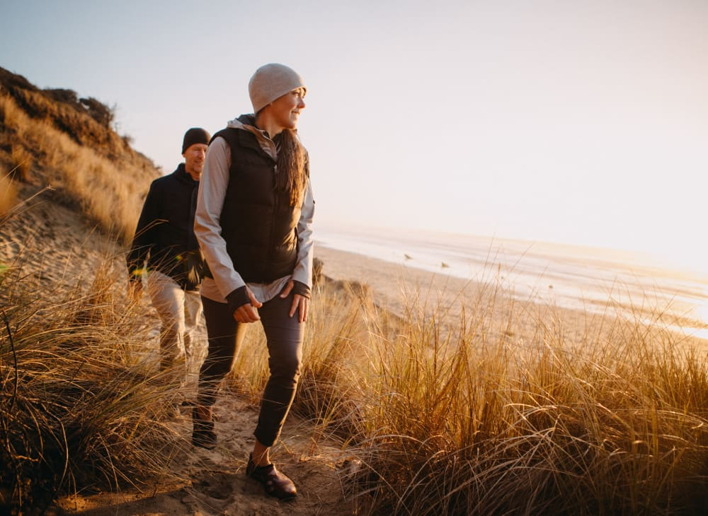 A couple takes a walk along a sandy beach near Serramonte Ridge Apartment Homes in Daly City, California
