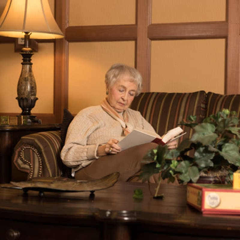 Assisted Living resident reading a book at York Gardens in Edina, Minnesota
