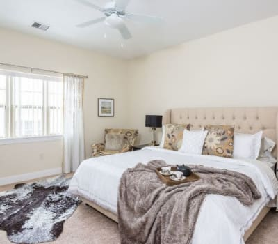 Bright bedroom with a ceiling fan at Gateway Landing on the Canal in Rochester, New York