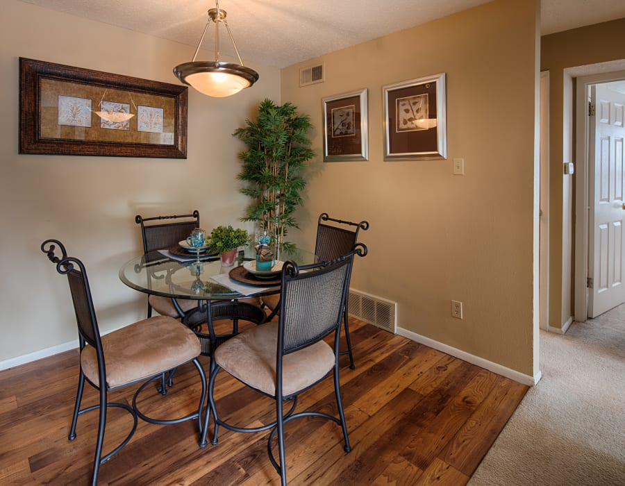Well-decorated dining area with custom lighting and hardwood flooring in a model home at Oxford Hills in St. Louis, Missouri