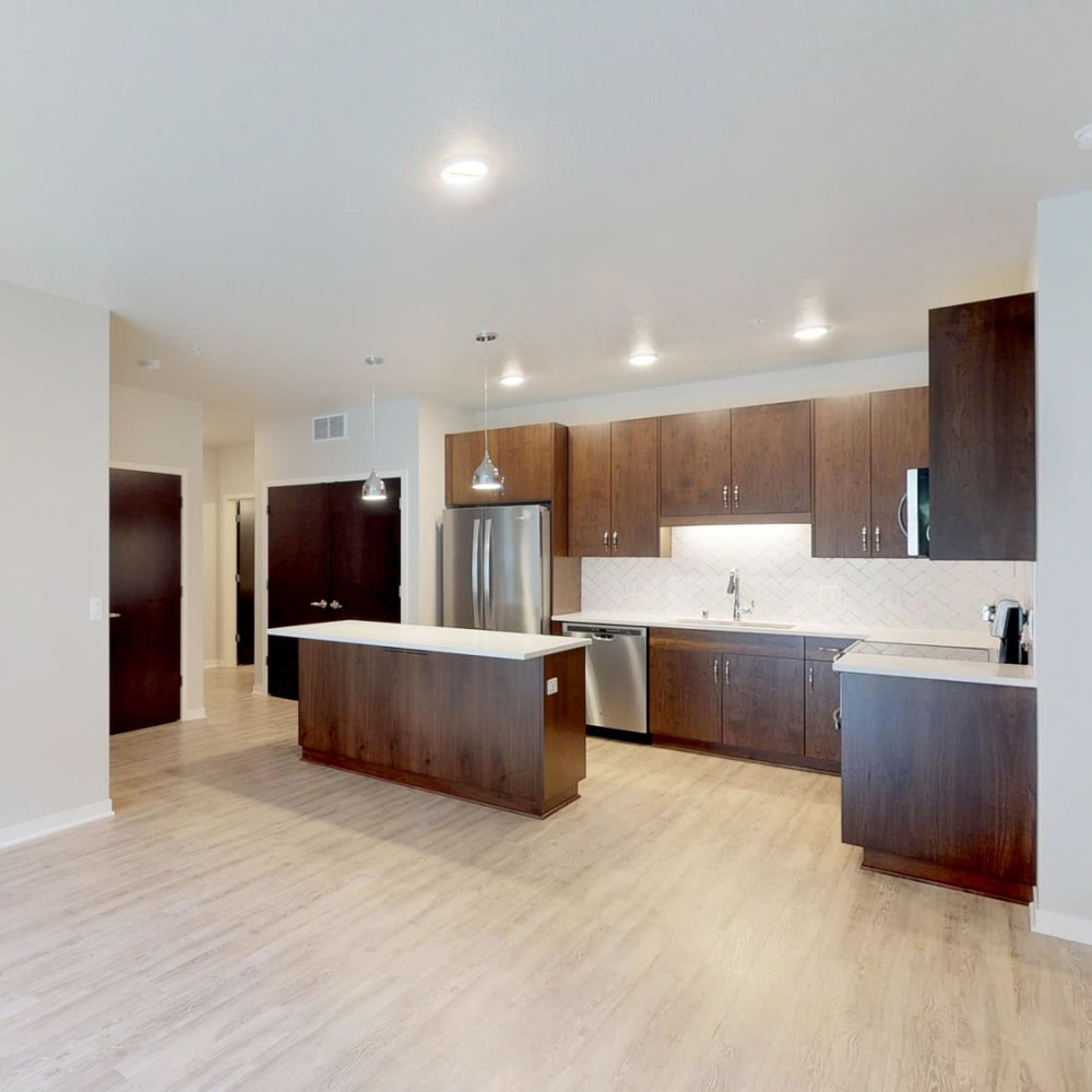 Beautiful hardwood floors and a chef-inspired kitchen in an open-concept model apartment at Oaks Union Depot in St. Paul, Minnesota