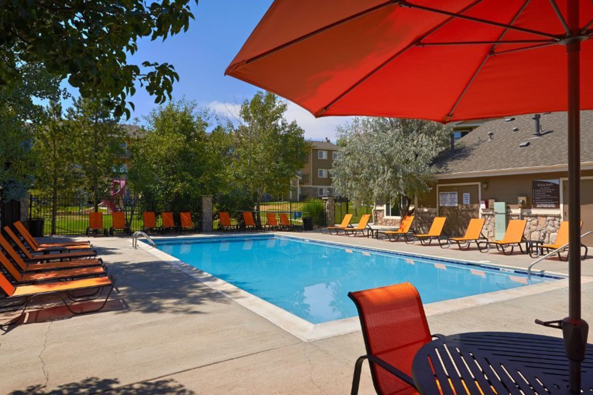 The pool surrounded by lush trees at Crossroads at City Center Apartments in Aurora, Colorado