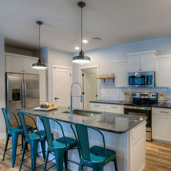 Gourmet kitchen with granite countertops and hardwood floors in model home at District Lofts in Gilbert, Arizona