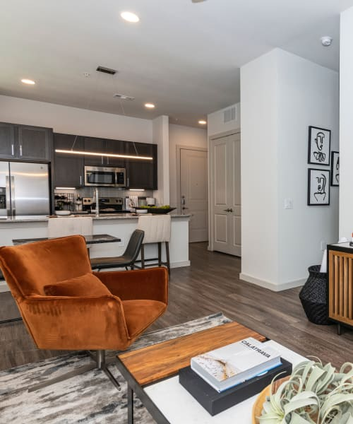 Living room with wood-style flooring at Magnolia on the Green in Allen, Texas