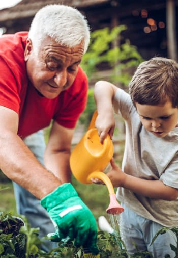 A resident and his grandson gardening at The Claiborne at Newnan Lakes in Newnan, Georgia.