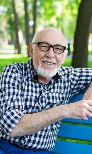 Older man sitting on a bench smiling at a Radiant Senior Living community