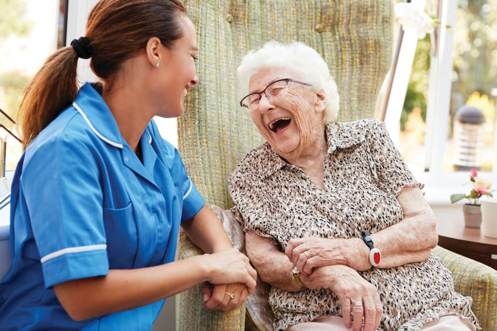 Caregiver and senior laughing together