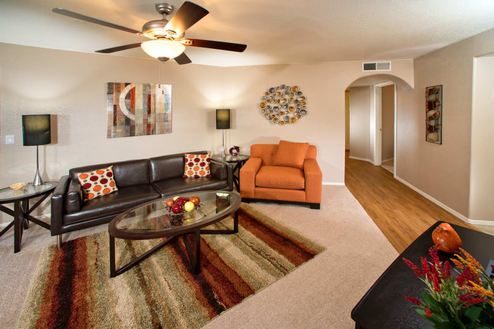 A living room layout with a ceiling fan and hardwood flooring at San Marin at the Civic Center in Scottsdale, Arizona