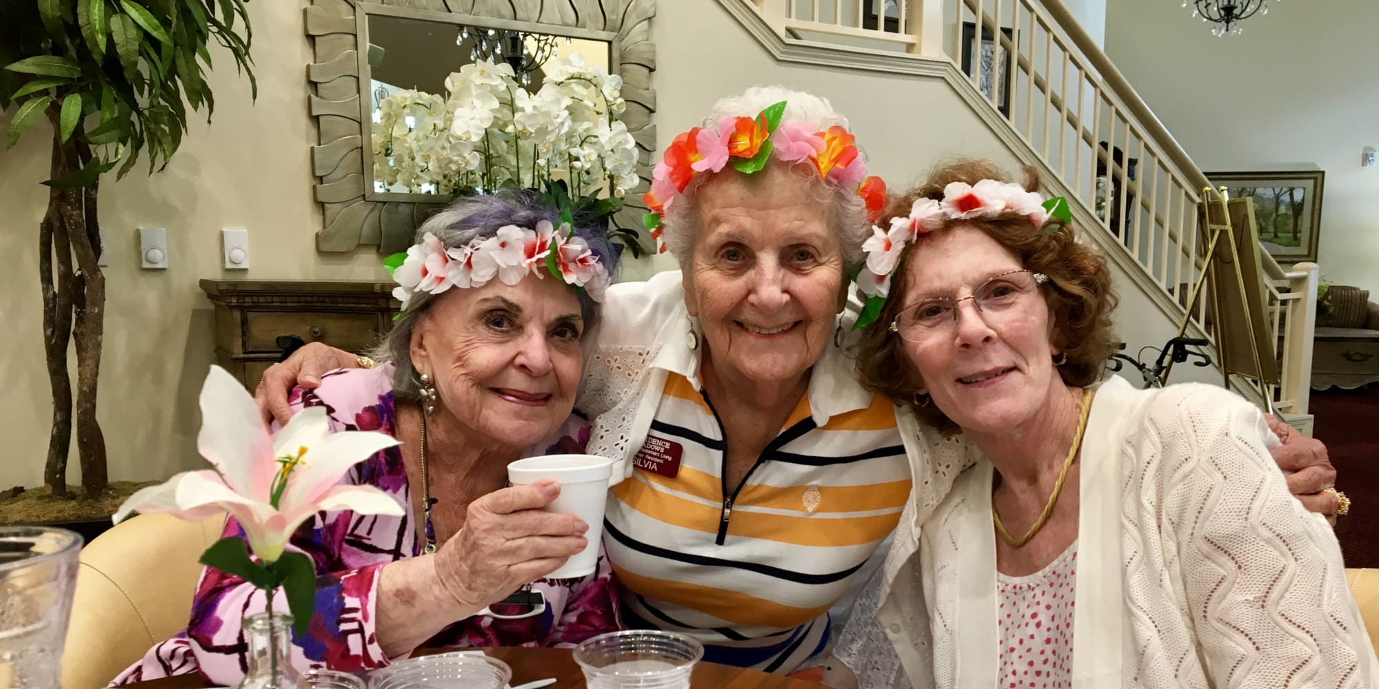Residents wearing leis at Providence Meadows Gracious Retirement Living in Charlotte, North Carolina