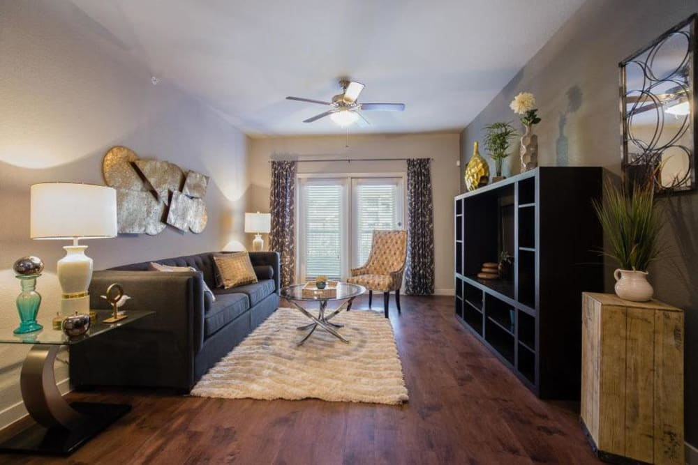 Faux-wood flooring and modern furnishings in a model home's living area at Verandas at Alamo Ranch in San Antonio, Texas