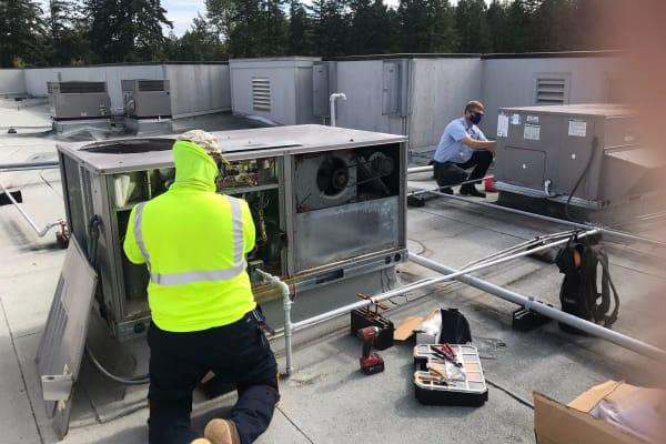 Workers installing an HVAC at  Patriots Glen in Bellevue, Washington.